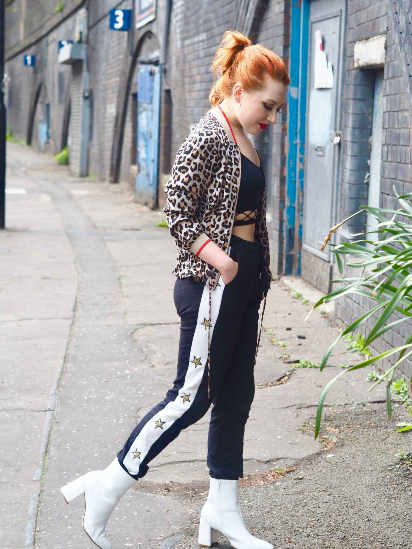 Blogger Styled by Alice wears the athleisure sports luxe trend by pairing a leopard print bomber with embellished black and white sweatpants and white heeled ankle boots
