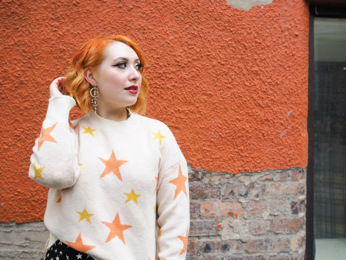 Scottish fashion blogger Styled by Alice shares easy ethical sustainable style tips wearing star jumper on orange background