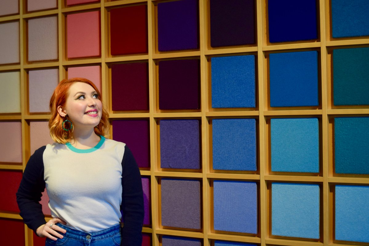 Scottish blogger Styled by Alice stands next to colourful wall of cashmere at Johnstons of Elgin visitor centre