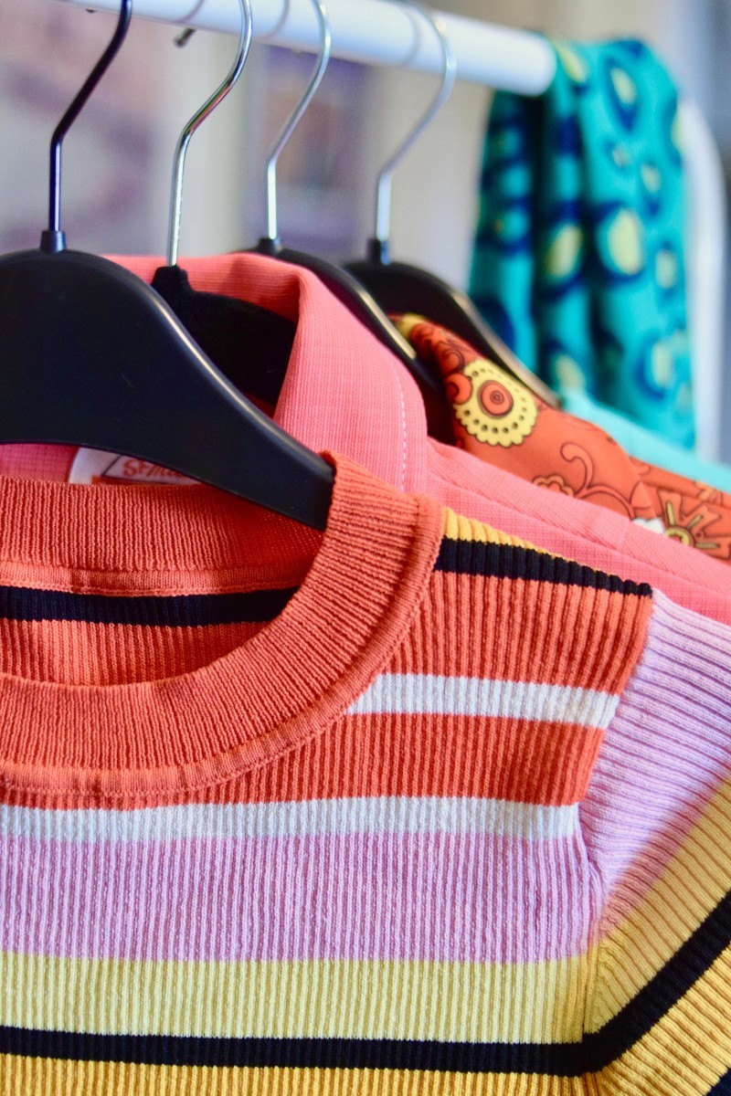 Colourful, orange toned shirts are used to show how to hang clothes properly