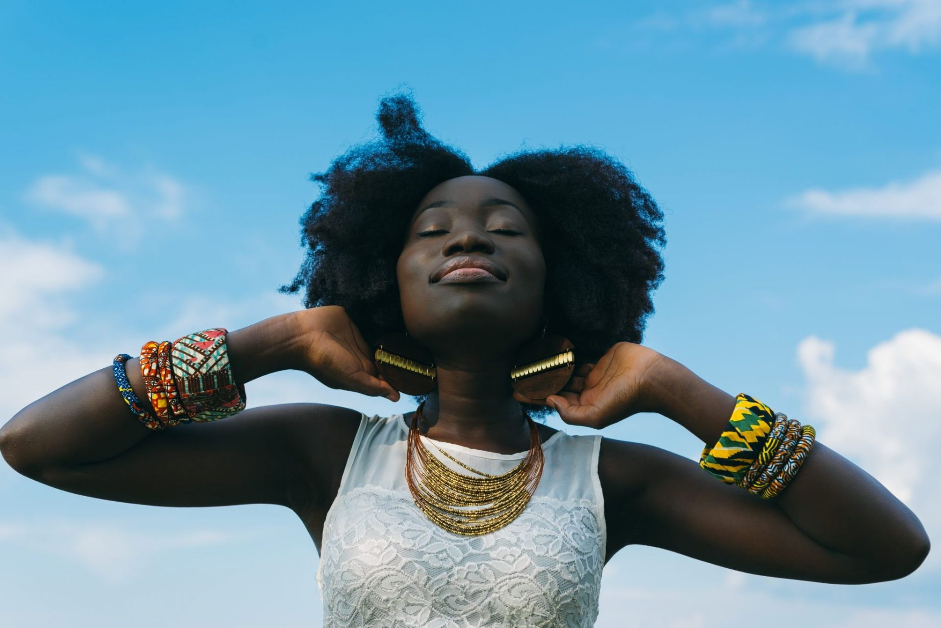 A black woman wearing colourful and fashionable African style jewellery