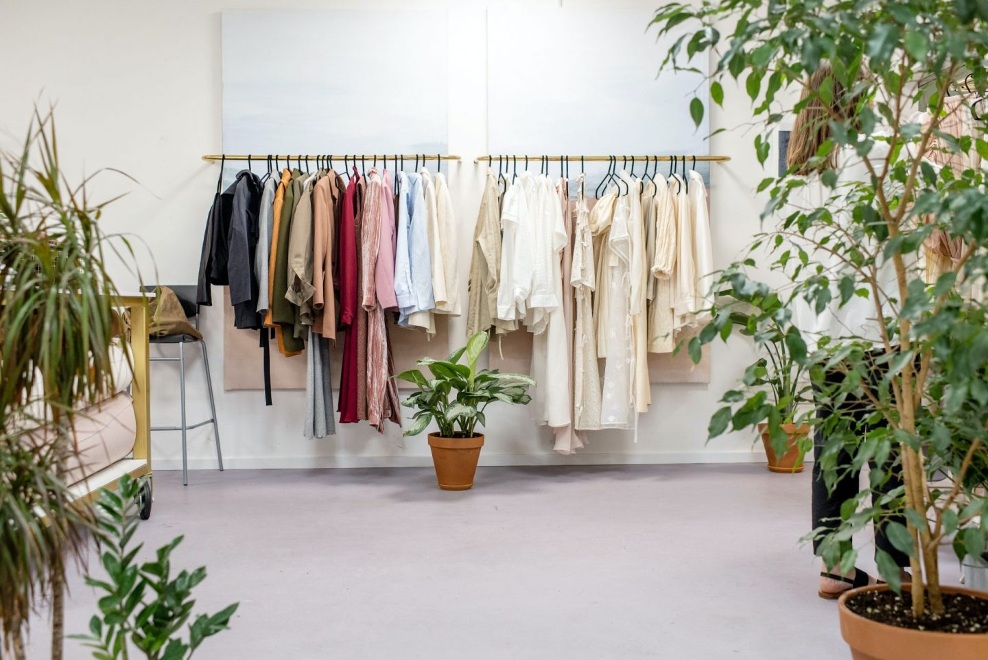 sustainable clothes hanging on a rail behind greenery