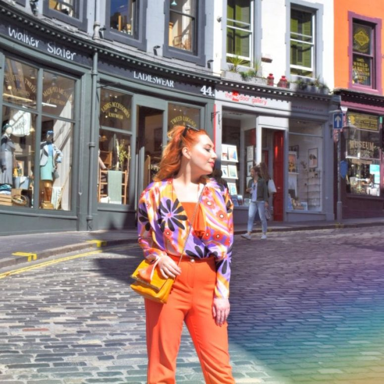 Edinburgh fashion stylist Alice wears a colourful orange and purple outfit on Victoria Street, Grassmarket