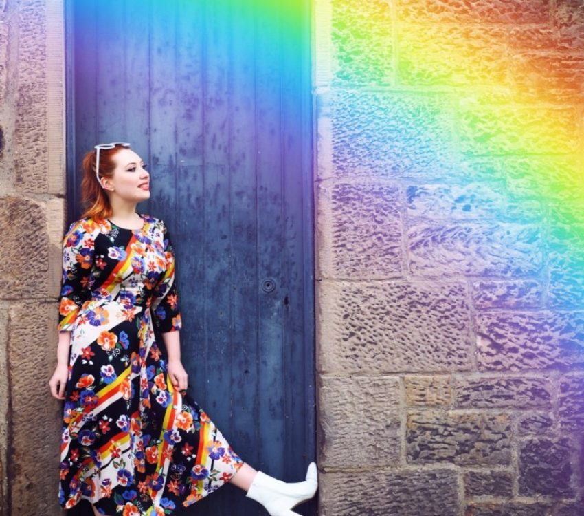 Styled by Alice wears a colourful floral dress with a rainbow above her